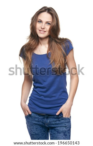 Smiling casual female in jeans and blue tshirt standing relaxed with hands in pockets feeling a little bashful, over white studio background - stock photo