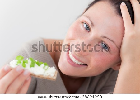 Smiling casual girl eating health care bread with vegetable - stock photo