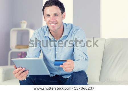 Smiling casual man holding tablet and credit card in bright living room - stock photo