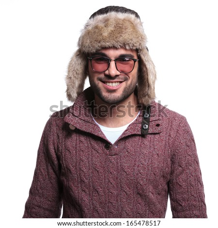 smiling casual man in winter clothes and furry hat, isolated on white background - stock photo