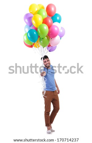 smiling casual man is offering a bunch of baloons on white background - stock photo