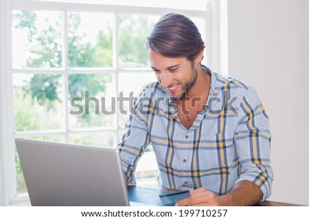 Smiling casual man using laptop to shop online at home in the living room - stock photo