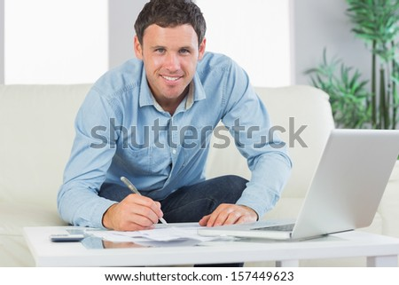 Smiling casual man writing on sheets paying bills in bright living room - stock photo
