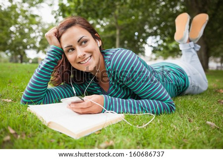 Smiling casual student lying on grass listening to music on campus at college - stock photo