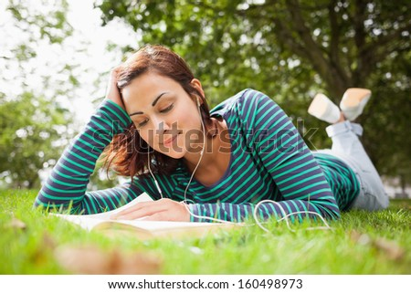 Smiling casual student lying on grass reading a book on campus at college - stock photo