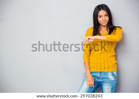 Smiling casual woman in sweater showing finger away over gray background - stock photo