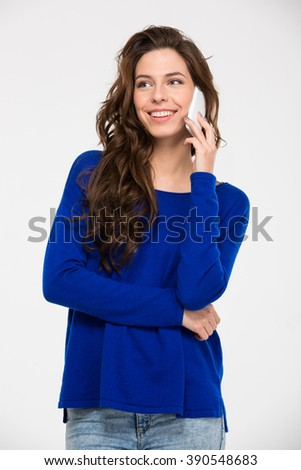 Smiling casual woman talking on the phone isolated on a white background - stock photo
