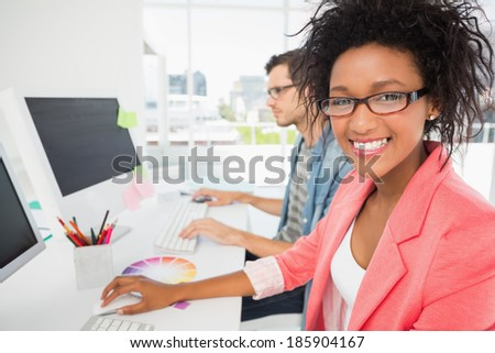 Smiling casual young couple working on computers in a bright office - stock photo