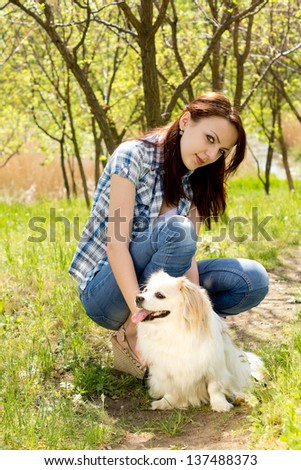 Smiling casual young woman crouched down beside her cute little long haired toy breed dog on a rural pathway - stock photo
