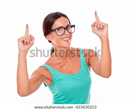 Smiling caucasian adult woman pointing upward with both hands while looking at the camera wearing glasses on a white background - stock photo