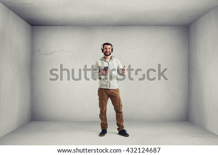 Smiling Caucasian bearded man in casual clothes and headphones is standing in empty white room and showing a thumb up gesture - stock photo