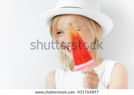 Smiling Caucasian child laughing and hiding behind red popsicle in her white beachwear summer clothes. Small blond girl looking sideways in playful manner of happy-go-lucky kid. - stock photo