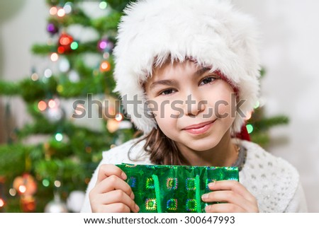Smiling Caucasian cute girl in white Santa hat holding green gift bag and looking at camera - stock photo