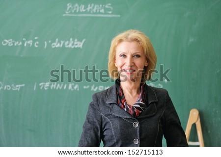 Smiling caucasian teacher on a chalkboard - stock photo