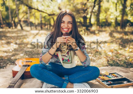 Smiling caucasian teen hipster girl sitting outdoors with guitar. Creative artistic young woman wearing casual clothes having a picnic with cupcake on autumn day. - stock photo