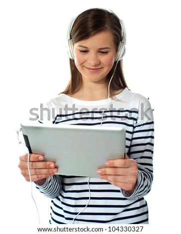 Smiling caucasian teenager enjoys listening to music. Studio shot - stock photo