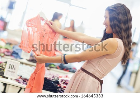 Smiling Caucasian woman choosing a shirt to buy at a boutique. - stock photo