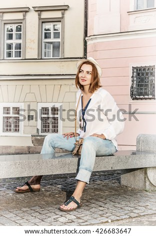 Smiling caucasian woman posing with sun hat on the bench in courtyard. Beauty and fashion. Facial expression. Women's fashion. - stock photo