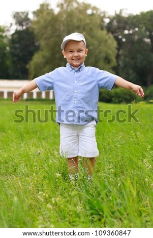 Smiling cheerful asian child in a cap and shorts in the park on a summer day - stock photo