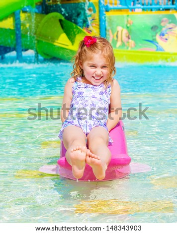 Smiling cheerful baby girl enjoying water attractions, warm sunny day, swimming in poolside, carefree childhood, summer vacation - stock photo