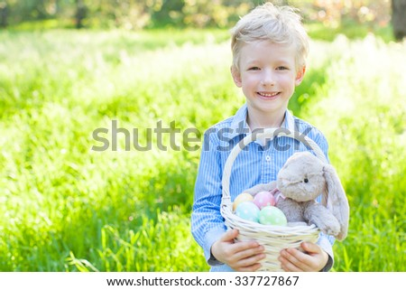 smiling cheerful boy holding basket with colorful easter eggs and bunny in the park enjoying spring time - stock photo