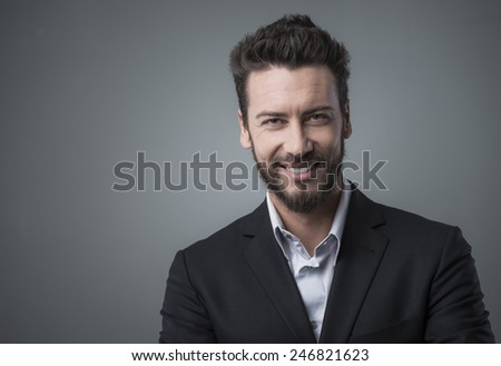 Smiling cheerful businessman posing on gray background - stock photo