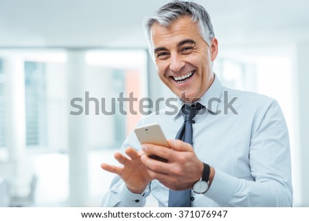 Smiling cheerful businessman using a touch screen smart phone and looking at camera - stock photo