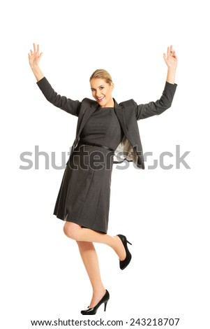 Smiling cheerful businesswoman with arms up - stock photo