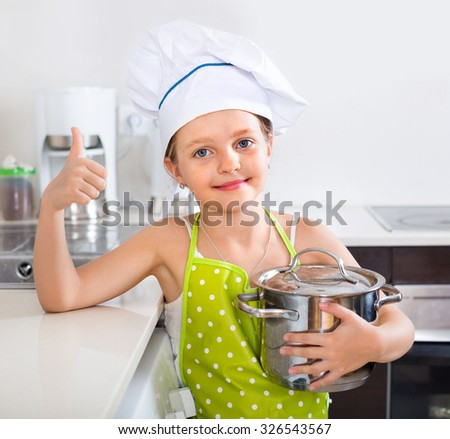 Smiling cheerful girl posing with pan indoors - stock photo