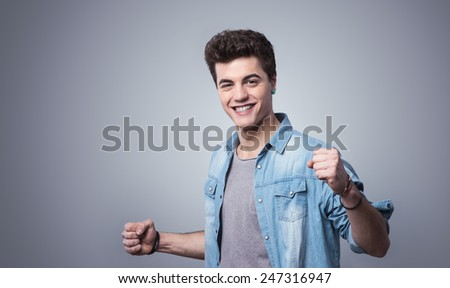 Smiling cheerful guy showing fists with playful attitude - stock photo