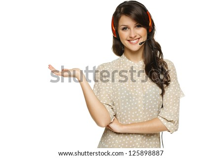 Smiling cheerful woman in headset holding empty copy space on her open palm, looking at camera, isolated on white background - stock photo