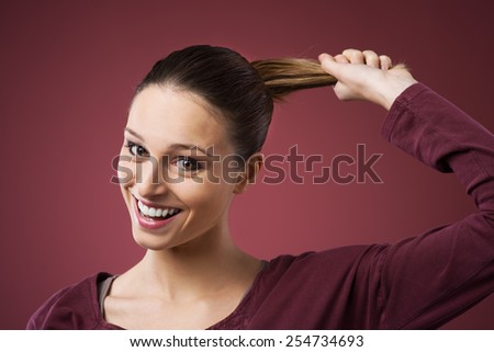 Smiling cheerful woman pulling her healthy strong hair - stock photo