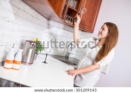 Smiling cheerful woman putting wine glass on the shelf at the her new kitchen - stock photo