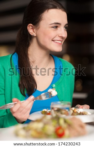 Smiling cheerful young girl having dinner - stock photo