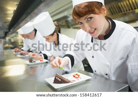 Smiling chef garnishing dessert plate in a busy kitchen - stock photo