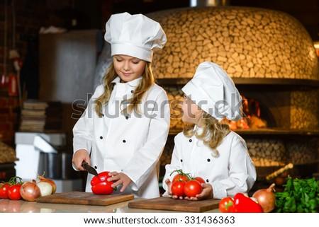 Smiling Chef girls preparing healthy food vegetable salad at restaurant kitchen - stock photo