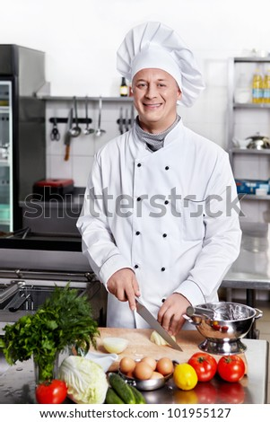 Smiling chef prepares in the kitchen - stock photo