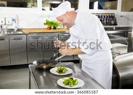 Smiling chef prepares steak dish at restaurant - stock photo