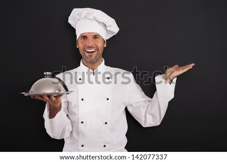 Smiling chef recommended main course - stock photo