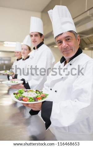Smiling Chef's presenting their salad in the kitchen - stock photo