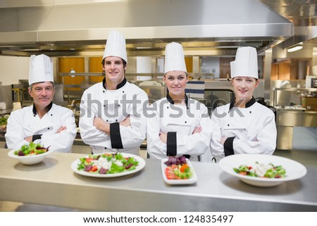 Smiling Chef's standing behind salads in the kithcen - stock photo