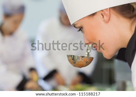 Smiling chef smelling the soup in kitchen - stock photo