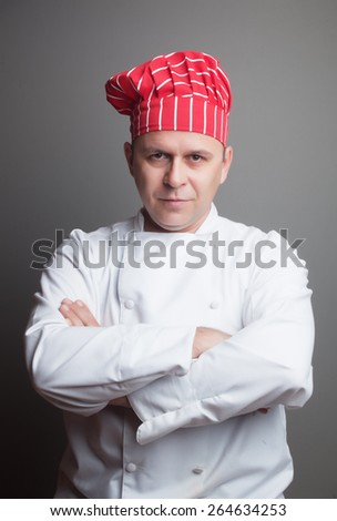 Smiling chef with red hat, studio shot over gray background - stock photo