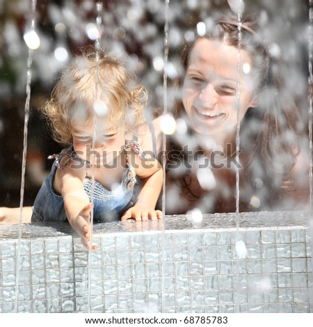 Smiling child and woman in fountain splashes - stock photo