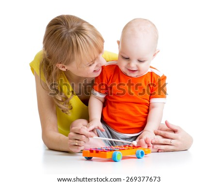 smiling child boy and mom playing with musical toy - stock photo