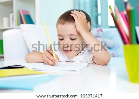Smiling child drawing in his exercise book - stock photo
