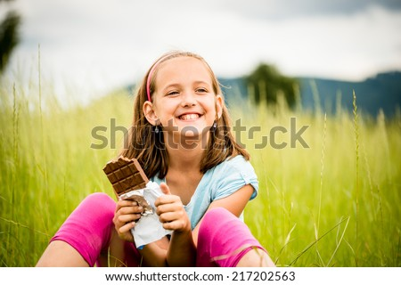 Smiling child eating and relishing chocolate - outdoor in nature - stock photo
