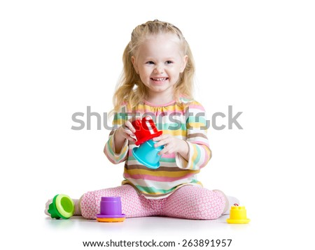 smiling child girl playing with color toys isolated on white - stock photo