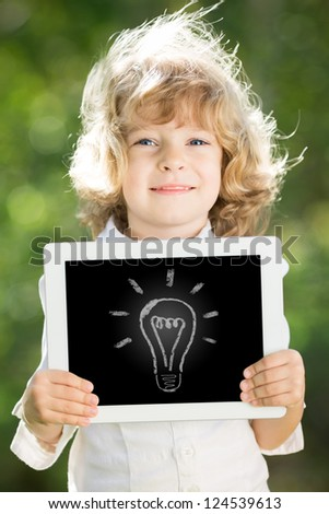 Smiling child holding tablet PC in hands. Idea concept - stock photo