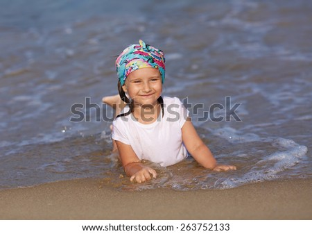 Smiling child in a white t-shirt lying in water on the beach on a clear sunny day. Shallow depth of field. Focus on the model's face. - stock photo